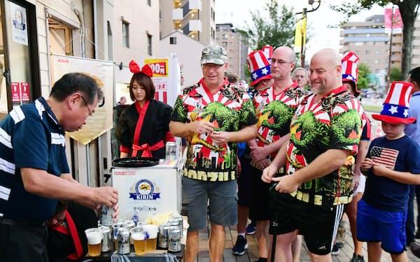 ラグビーW杯の観戦に向かう途中、ビールを購入する外国人(26日、神戸市兵庫区)