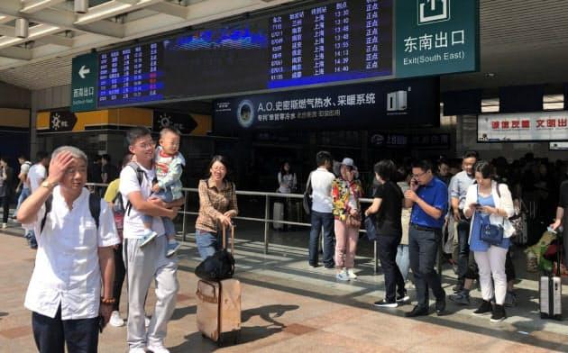 国慶節をひかえ早くも旅行や帰省に出る人で駅はにぎわう(高速鉄道の上海駅)