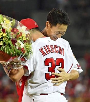 試合後の引退セレモニーで、菊池涼(手前)から花束を贈られ抱き合う広島の赤松真人外野手(27日、マツダスタジアム)=共同
