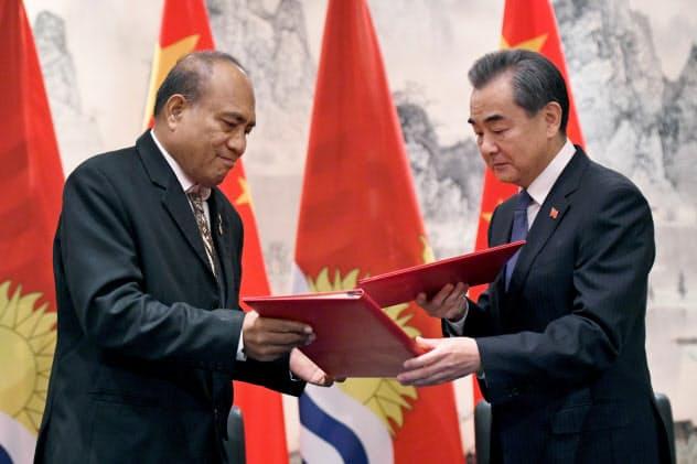 国交樹立の文書を交換するキリバスのマーマウ大統領(左)と中国の王毅外相(27日、ニューヨーク)=ロイター
