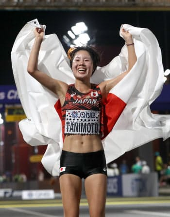 日本人トップの7位でゴールし、笑顔で日の丸を掲げる谷本=山本博文撮影