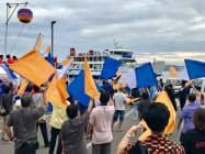 瀬戸芸秋会期が開幕し、関係者がフェリー入港を歓迎した(28日午前、香川県丸亀市の本島)