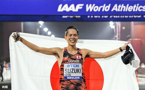 世界陸上の男子50キロ競歩で優勝し、笑顔で日の丸を掲げる鈴木雄介(29日、ドーハ)=共同