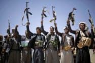 フーシはサウジへの攻撃を繰り返している(21日、イエメン首都サヌアで銃をかかげるイエメンの親イラン武装勢力フーシ)=ロイター