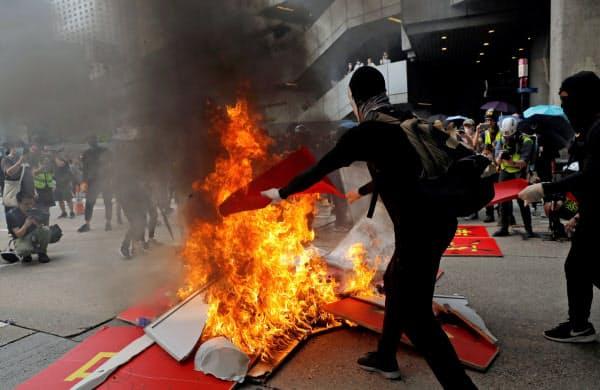 29日、デモ隊は中国建国70周年を祝う看板を燃やした=ロイター