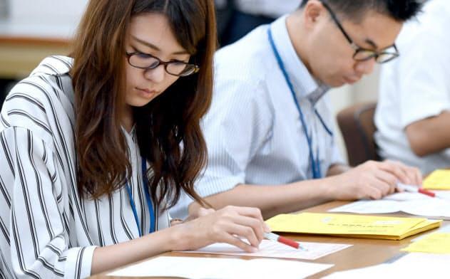 願書をチェックする大学入試センターの職員(30日午前、東京都目黒区)