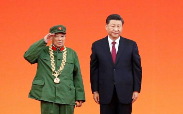 29日、建国70年に合わせて退役軍人に勲章を授与した習国家主席(右)=ロイター