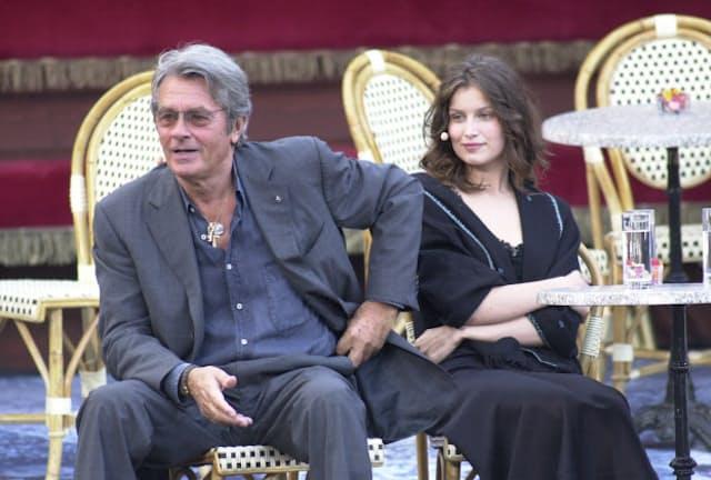 2002年、フランスのモデルであるレティシア・カスタ(右)と。シックなスーツを洒脱(しゃだつ)に着こなしている=AP