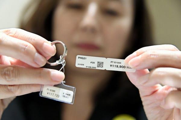 消費増税を前に指輪の値札を張り替える店員(30日、東京都中央区の松屋銀座)