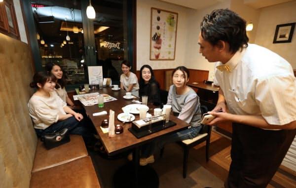 消費増税対応で、24時間営業をやめ午前0時閉店を伝えるファミリーレストランの店員(右)=30日夜、東京都中央区のデニーズ東銀座店