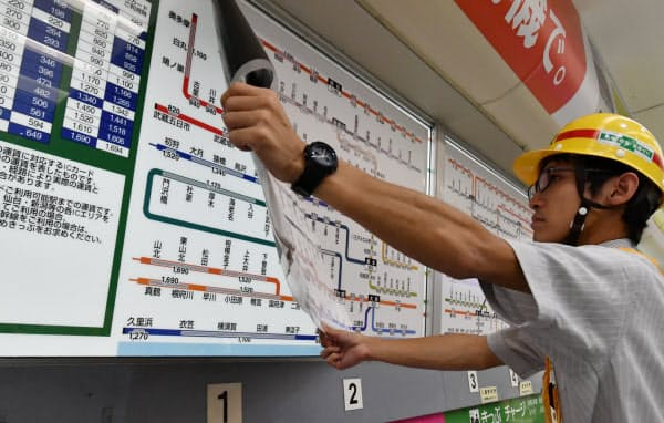 消費増税にあわせ、張り替えられる運賃表(1日未明、JR新宿駅)