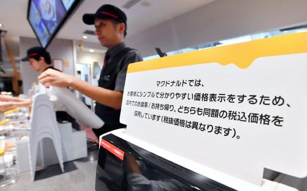 税込み価格を店内、持ち帰りとも同額に調整する告知文をレジに掲示したマクドナルドの店舗(1日午前、東京都新宿区のマクドナルド西新宿店)