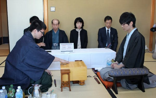 王座戦第3局で初手を指す永瀬拓矢叡王(左)=1日午前、神戸市のホテルオークラ神戸