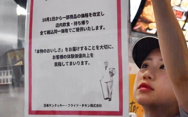 店内、持ち帰りとも税込み同額で提供する知らせを店頭に張る店員(1日午前、東京都文京区のケンタッキーフライドチキン東京ドームシティラクーア店)
