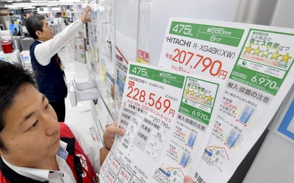 税込み表示を目立たせる値札(左下)に付け替える家電量販店の店員(1日午前、東京都千代田区のビックカメラ有楽町店)