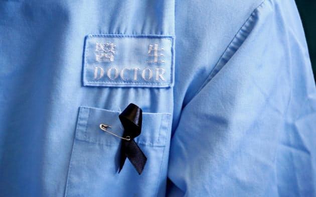 抗議の意思を示すリボンをつけ、警察の弾圧を批判する香港の医師=ロイター