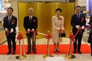 記念式典でテープカットを行う青木和宏店長(左)と小柴夫妻(中)