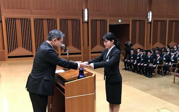 関西みらいフィナンシャルグループ(FG)の菅哲哉社長(左)が内定者に内定通知書を渡した