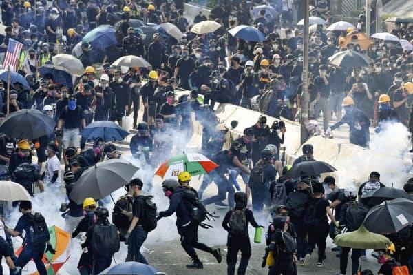 香港で「逃亡犯条例」改正案を発端とした抗議活動中、警官隊に催涙弾を撃ち込まれ逃げ惑うデモ隊(1日)=共同