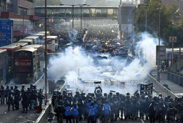 香港で「逃亡犯条例」改正案を発端とした抗議活動をするデモ隊(奥)に、警官隊が催涙弾を撃ち込み現場に立ち込める煙(1日)=共同