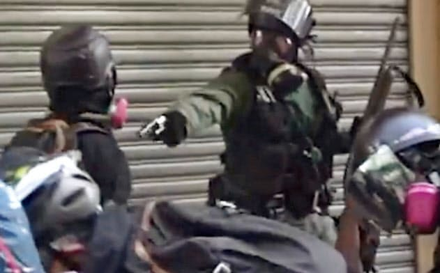 1日、香港でデモ参加者(左)に向けて発砲したとされる警察官の映像(香港大学生会Campus TVのフェイスブックから・共同)