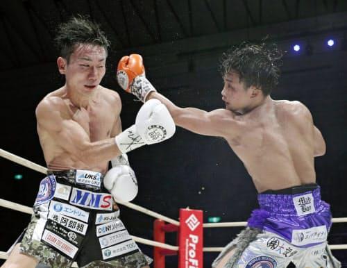 6回、久田哲也(左)を攻める京口紘人。判定勝ちし、2度目の防衛に成功した(1日、エディオンアリーナ大阪)=共同