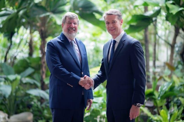 握手するマイナー・インターナショナルのウィリアム・ハイネキ会長(左)とベリタ・ヘルスケアグループのジュリアン・アンドリーズ最高経営責任者(CEO)