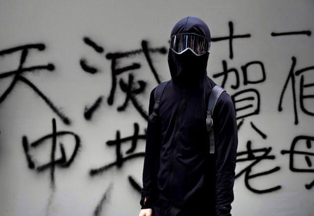 完全に顔を覆うデモ参加者もいる(1日、香港)=AP