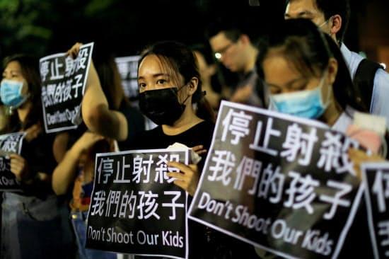「私たちの子どもを撃つな」と書かれた紙を掲げる人たち(2日、香港)=ロイター