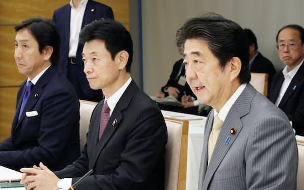 経済財政諮問会議であいさつする安倍首相。中央は西村経財相(9月30日、首相官邸)
