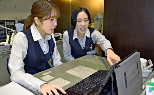 親和銀行の端末の使い方を十八銀行の女性行員(右)が学んでいる(長崎市の親和銀行大波止支店)