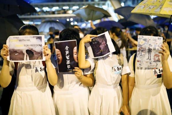 「覆面禁止規則」制定に反対し、顔を隠してデモ行進する若者ら=4日、香港(共同)