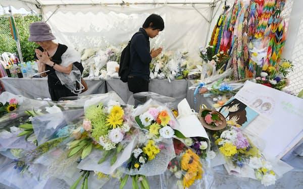 京都アニメーション放火殺人事件で犠牲者の冥福を祈り献花台で手を合わせる人たち(8月、京都市伏見区)