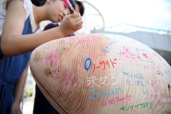 ラグビーボールをかたどった木材に書かれた応援メッセージ