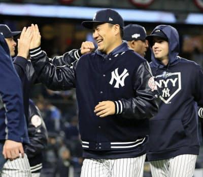 ツインズに勝利しチームメートとタッチを交わすヤンキース・田中(4日、ニューヨーク)=共同