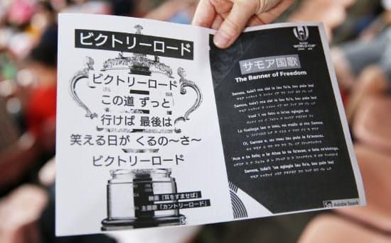 試合前、有志が観客に配っている歌詞カード。サモアの国歌と日本代表のチームソングの歌詞を紹介し、一緒に歌おうと呼びかけている