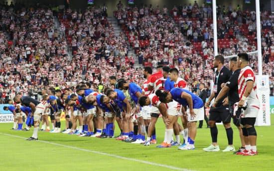 試合後、観客の声援に応える両チームの選手たち
