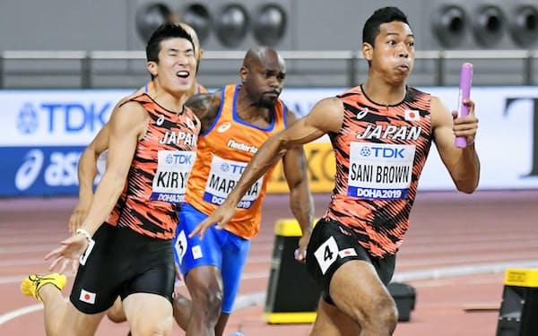陸上の世界選手権男子400メートルリレー決勝で、第3走者の桐生(左)からバトンを受け走りだすアンカーのサニブラウン(右)=共同