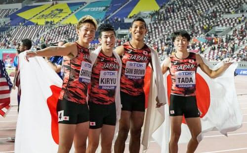 陸上の世界選手権男子400メートルリレー決勝でアジア新をマークして3位に入り、日の丸を背に笑顔でポーズをとる(左から)白石、桐生、サニブラウン、多田。東京五輪出場権も確保した(5日、ドーハ)=共同