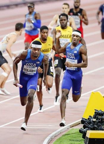 男子1600メートルリレー決勝 バトンを受け走りだす米国チームのアンカーのベンジャミン(手前左)。2分56秒69で優勝した(6日、ドーハ)=共同