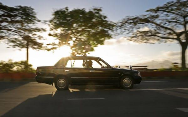 夕暮れの道路を日本でおなじみの直線的なフォルムのタクシーが走る(スバ)