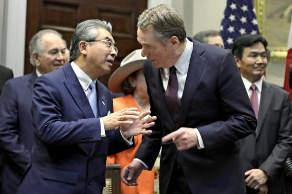 日米貿易協定への署名に際し、言葉を交わす日本の杉山晋輔駐米大使(左)とライトハイザーUSTR代表(7日、ホワイトハウス)=AP