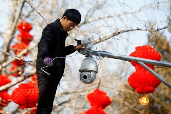 米国は中国の監視カメラ最大手ハイクビジョンを調達禁止の対象としている(北京で同社製品を設置する作業員)=ロイター