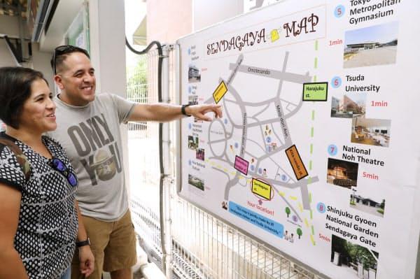 津田塾大学の梅五輪プロジェクトで作った千駄ケ谷駅周辺の英語マップを見る訪日外国人(東京都渋谷区)