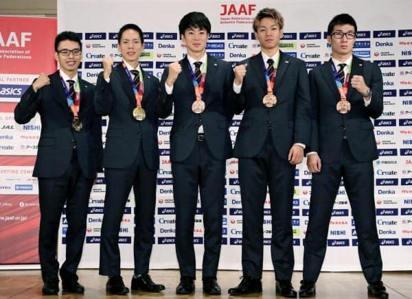 記者会見でポーズをとる(左から)男子20キロ競歩で金メダルの山西利和、男子50キロ競歩で金メダルの鈴木雄介、男子400メートルリレーで銅メダルの多田修平、白石黄良々、桐生祥秀(8日午前、東京都内)=共同