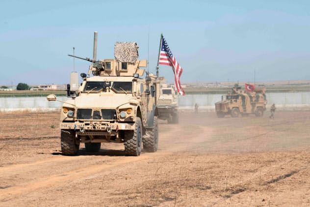 シリアからの米軍撤収で混乱拡大も(9月、トルコ軍とシリア北東部をパトロールする米軍車両)=ロイター