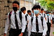 8日、香港ではマスク姿で登校する生徒が目立った=ロイター