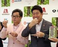 記者会見で大福をほお張る川崎市の福田紀彦市長(右)とスエヒロの三藤哲也社長