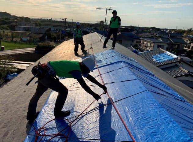 各地から駆けつけた職人たちが屋根にブルーシートを張った