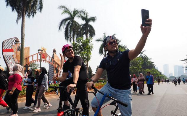英国製の折りたたみ自転車に乗りながら、SNSで写真を共有する(ジャカルタ中心部)